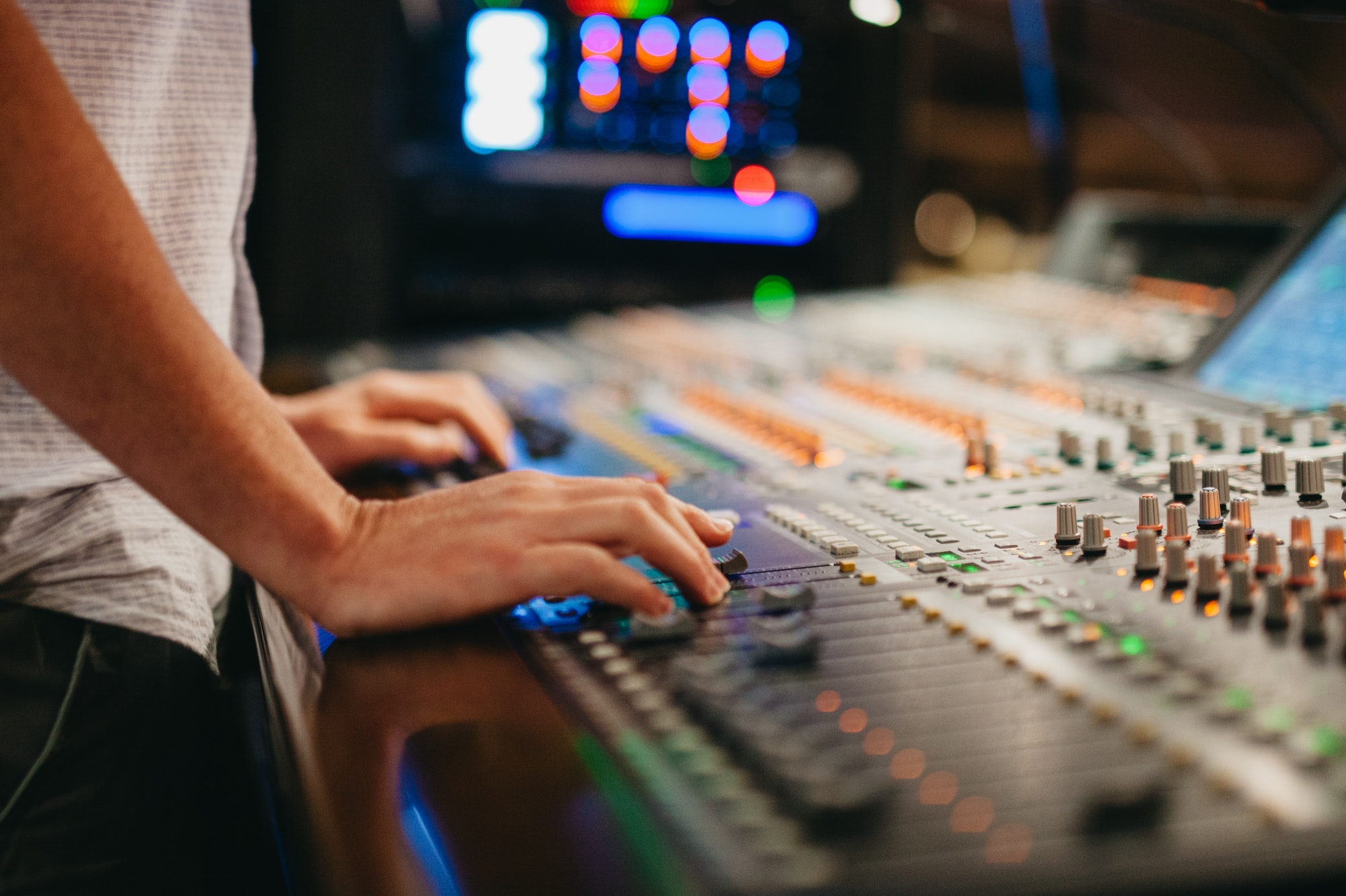 A sound tech works on a mixing board changing levels of the music production.