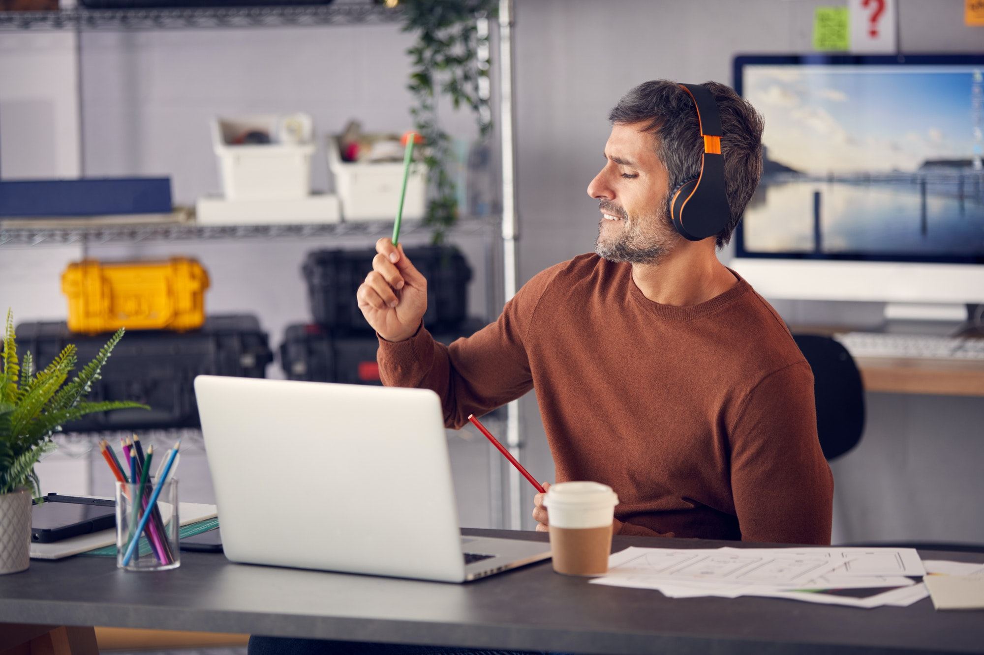 Male Advertising Marketing Or Design Creative With Wireless Headphones Air Drumming At Desk